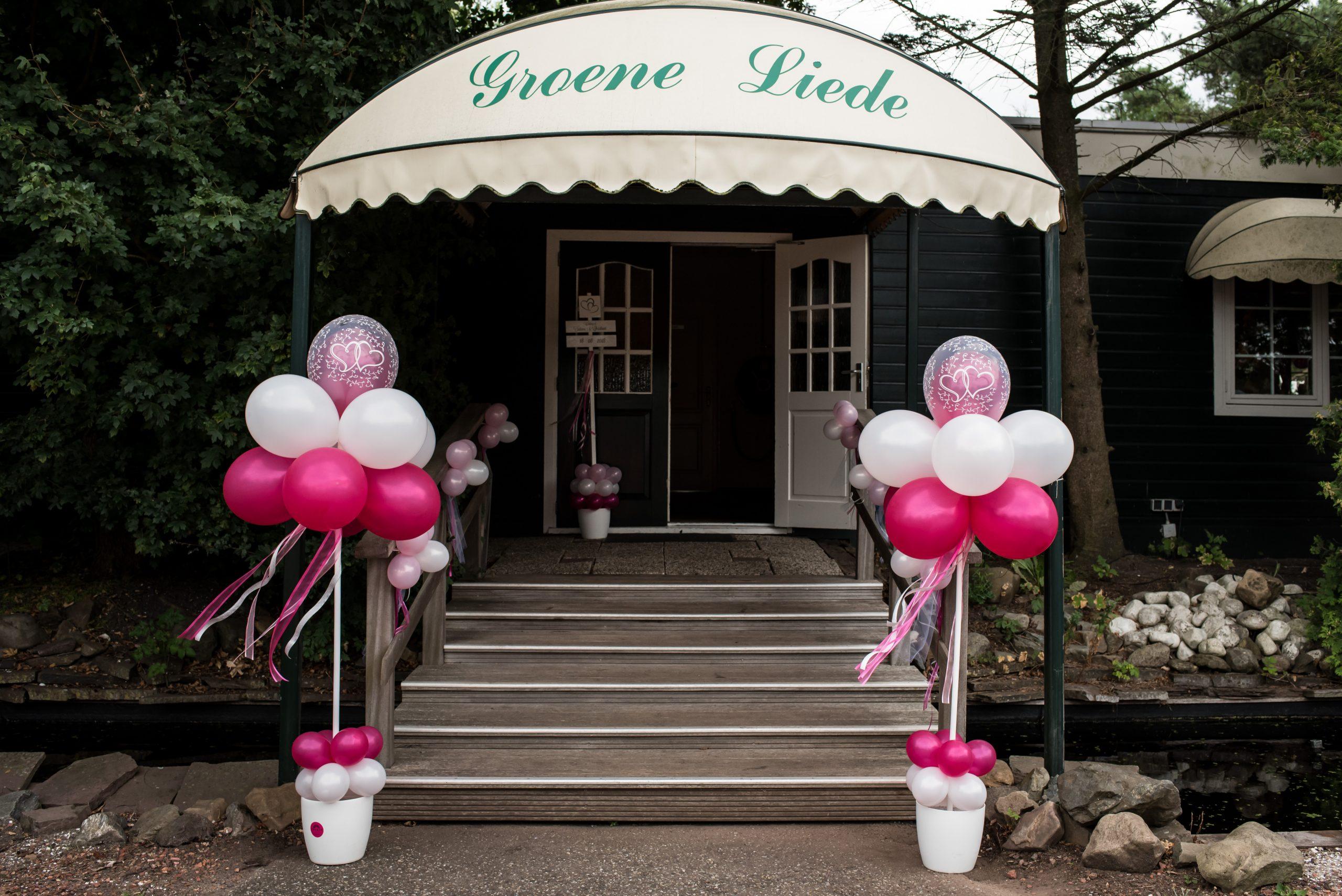 Trouwlocatie feestlocatie entree met wit en roze ballonen