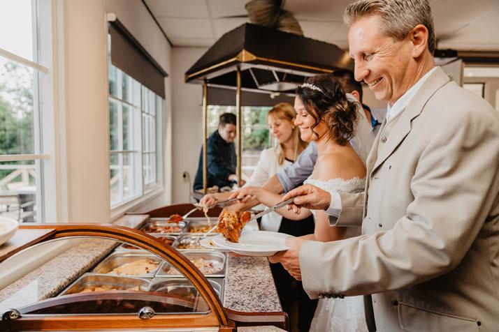 Trouwlocatie feestlocatie Buffet met bruidpaar met gast en kok op achtergrond