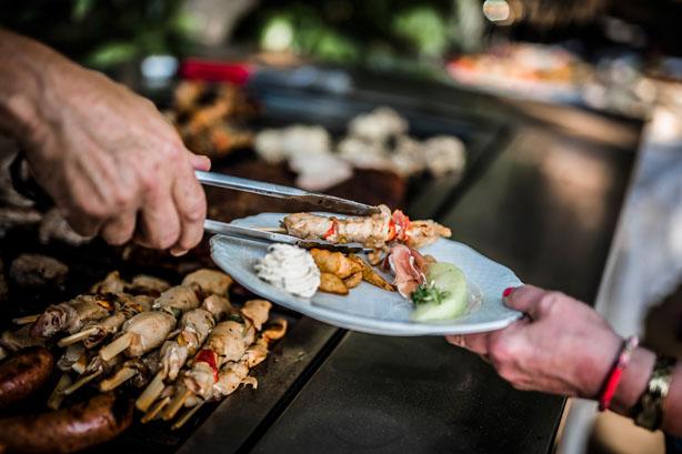 Trouwlocatie feestlocatie Buffet met chef die gasten van vlees voorziet vanaf de barbeque