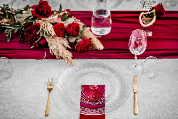 Trouwlocatie feestlocatie Diner tafel ingedekt met glazen bord en rood thema