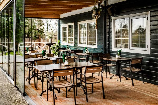 Trouwlocatie feestlocatie terras met glazen wand en losse diner tafels