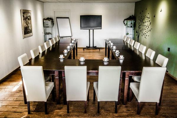 Vergaderlocatie met vergader opstelling en koffie op tafel