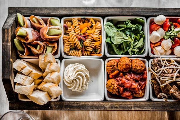 trouwlocatie Shared diner met stokbrood, kruidenboter, ham met meloen, pasta salade, gehaktballetjes, salade caprese en ossenhaas reepjes