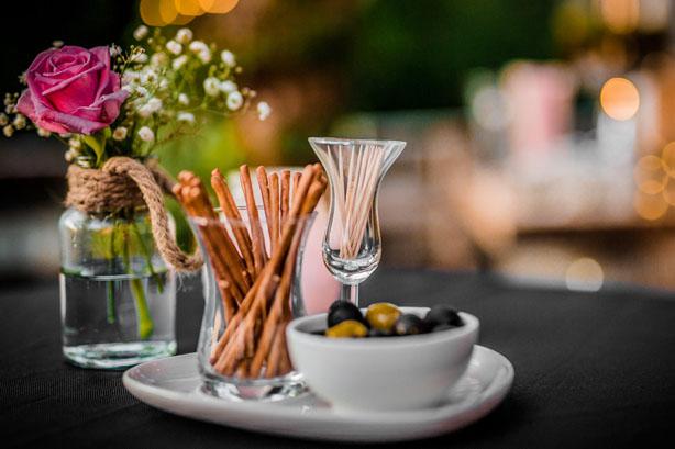 Trouwlocatie feestlocatie Tafel garniring met pretzel stokjes en olijven